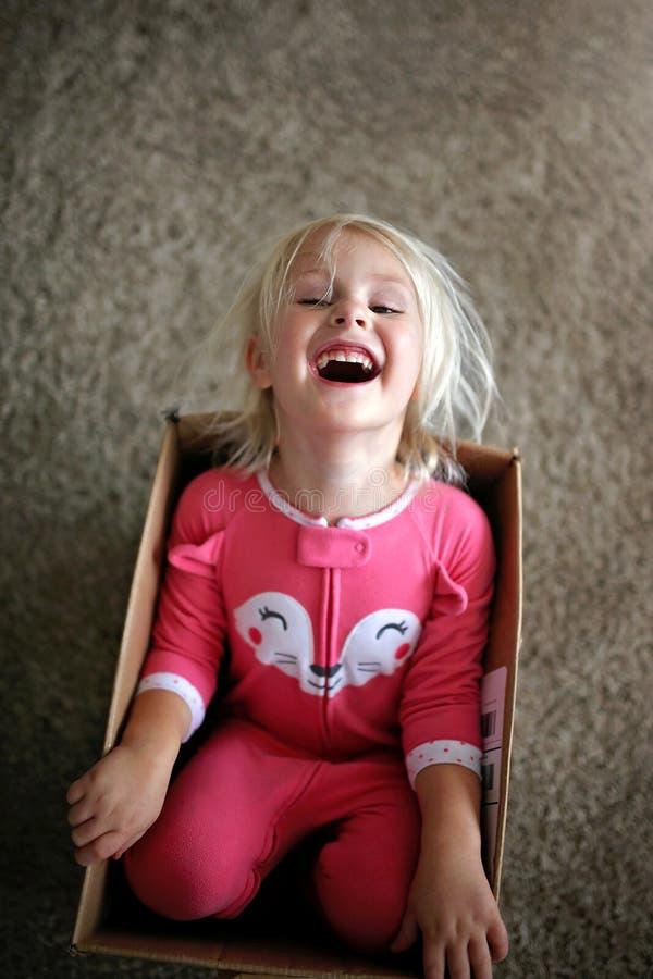Bambino piccolo di risata che gioca in grande scatola di cartone a casa immagini stock