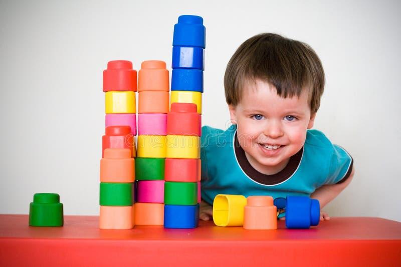 Bambino piccolo di risata con costruzione variopinta immagine stock