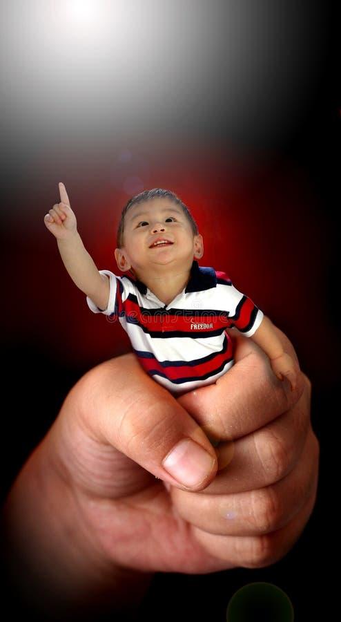 Bambino piccolo in grande mano fotografia stock