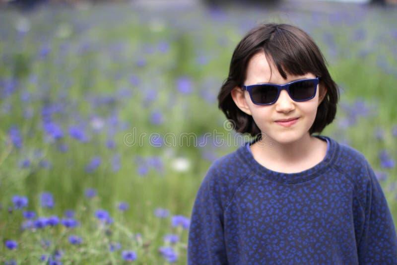 Bambino piccolo sorridente con gli occhiali da sole che cammina sopra il giardino vago del fiordaliso fotografie stock