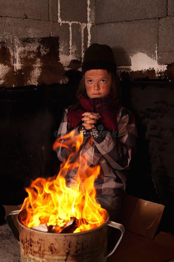 Bambino povero del mendicante che si scalda al fuoco in un vaso della latta immagine stock