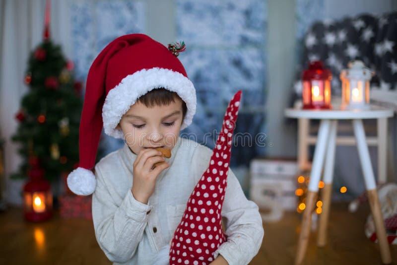Bambino prescolare sveglio, ragazzo, leggente un libro e mangiante i biscotti a fotografia stock