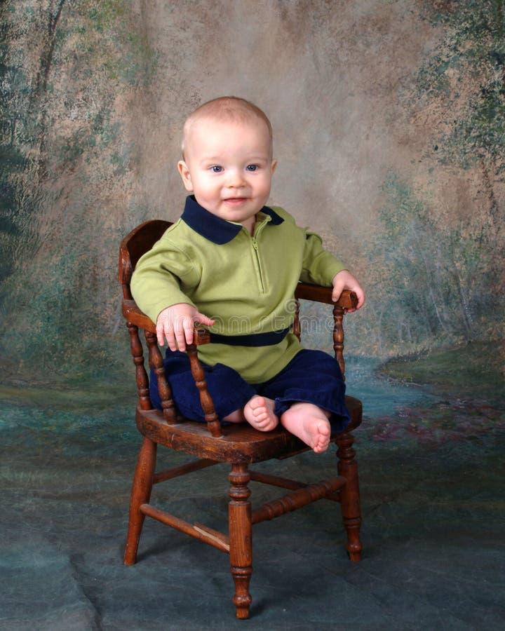 Bambino in presidenza di legno fotografie stock