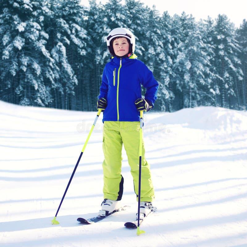 Bambino professionale dello sciatore che porta gli abiti sportivi con gli sci nell'inverno fotografia stock