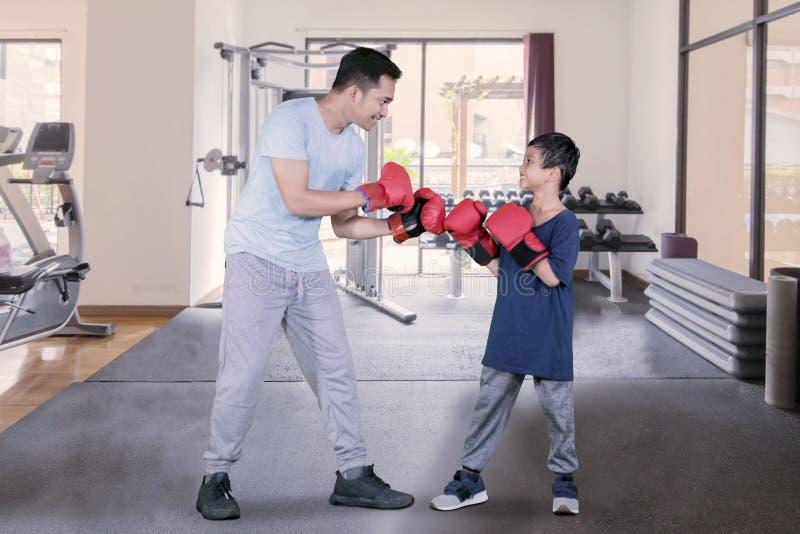 Bambino pronto a combattere con suo padre nel centro della palestra fotografia stock libera da diritti
