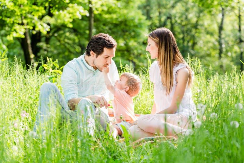 Bambino proteggente della famiglia che prende figlio nel mezzo fotografia stock