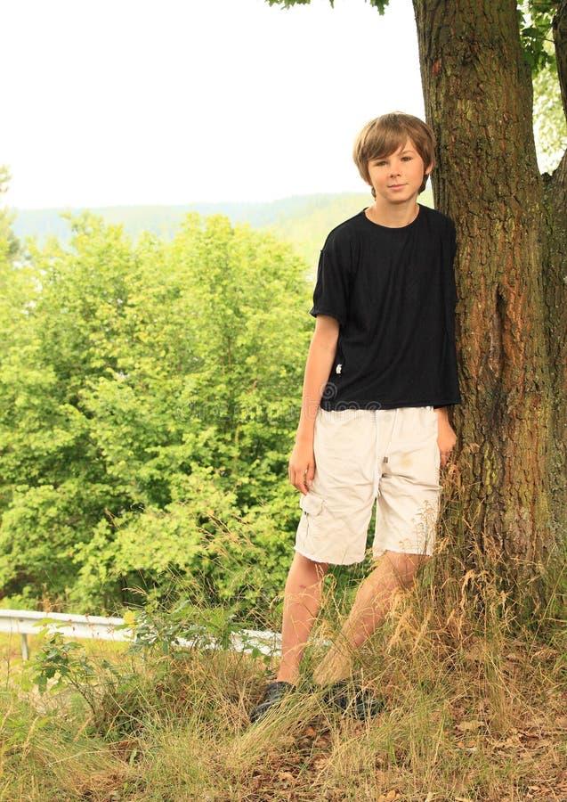 Bambino - ragazzo che si appoggia albero fotografia stock