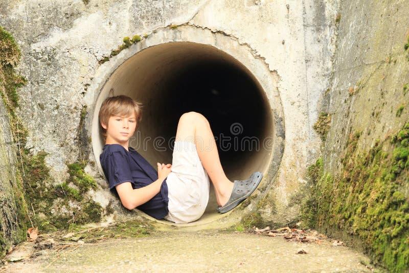 Bambino - ragazzo che si siede nel chiusa-modo fotografia stock