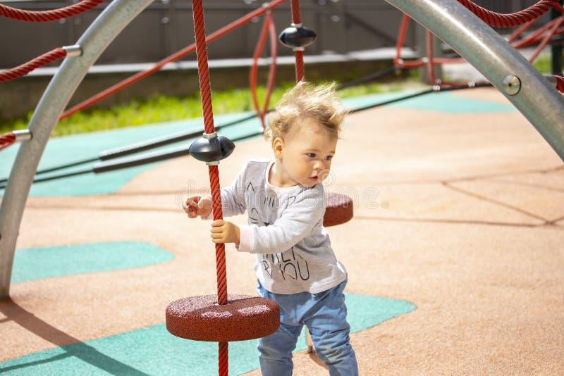 Bambino ragazzo della ragazza da 1 anno, caucasico sul campo da giuoco, capelli biondi d'ondeggiamento immagine stock libera da diritti
