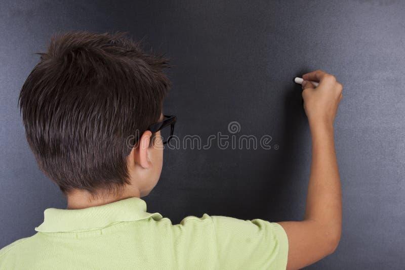 Bambino a scrittura della scuola immagine stock