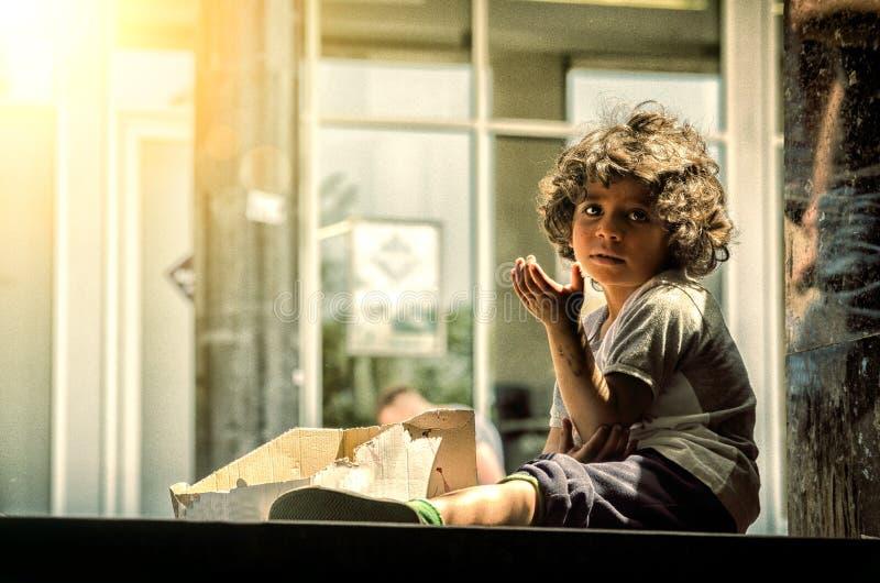 Bambino senza tetto affamato dell'orfano del mendicante sulla via che esamina la macchina fotografica con luce solare Maggio - 20 immagine stock libera da diritti