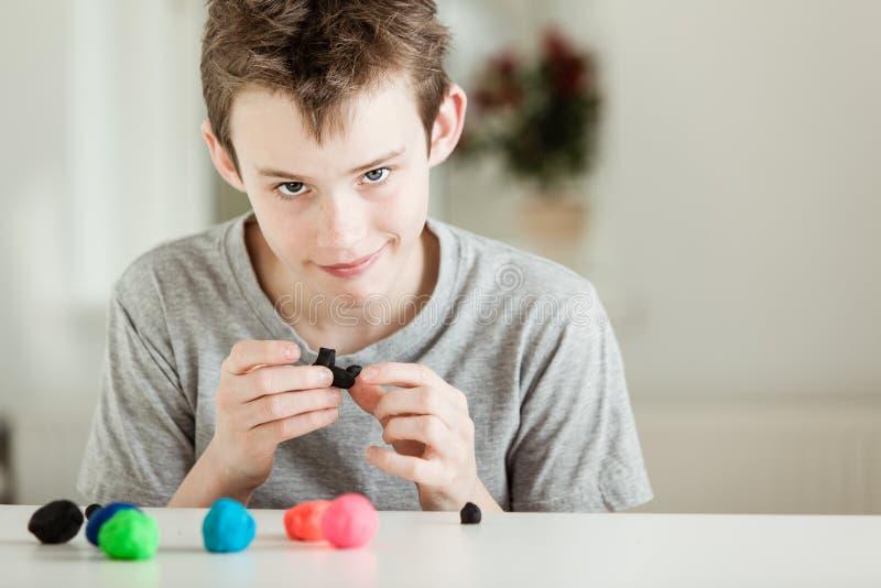 Bambino Smirking che gioca con i pezzi di argilla immagine stock libera da diritti