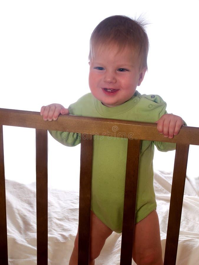 Bambino sorridente alla culla della stanza della scuola materna immagine stock