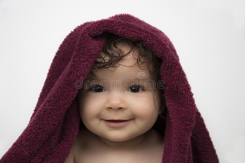 Bambino sorridente in asciugamano di bagno rosso immagini stock