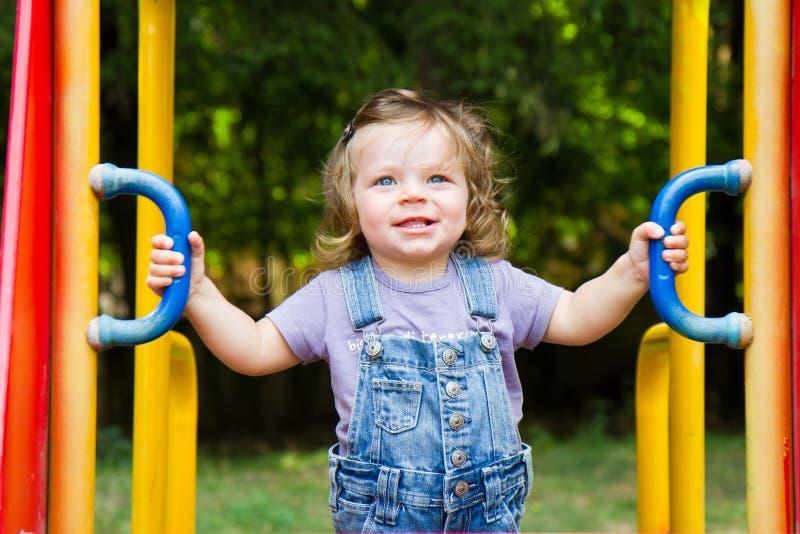 bambino sorridente che gioca in un'area del campo da giuoco fotografie stock