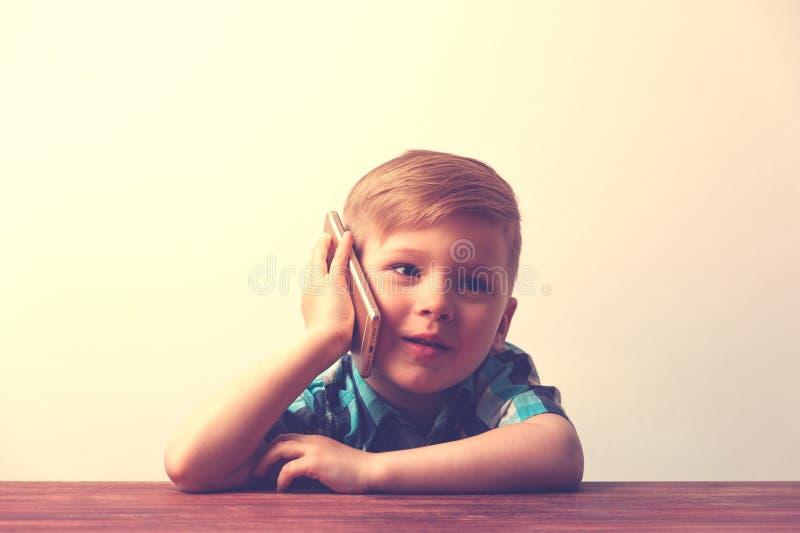 Bambino sorridente che per mezzo dello smartphone fotografia stock libera da diritti