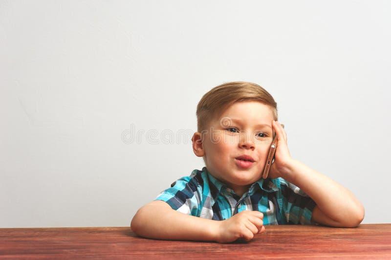 Bambino sorridente che per mezzo dello smartphone immagine stock