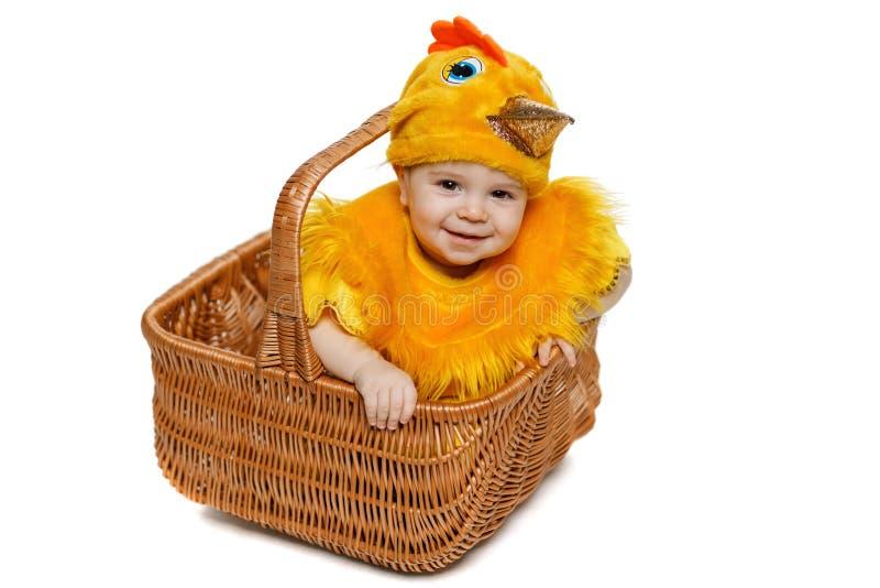 Bambino sorridente che si siede nel canestro di Pasqua in costume del pollo fotografia stock