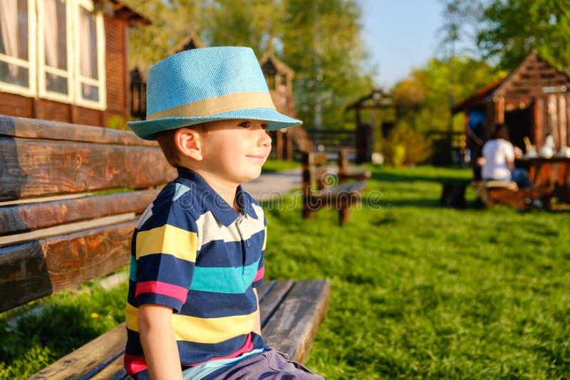 Bambino sorridente che si siede su un banco di parco con il prato verde su fondo fotografia stock