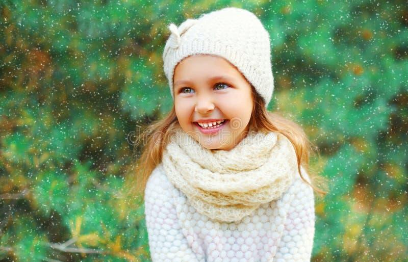 Bambino sorridente della bambina che porta un maglione tricottato del cappello con la sciarpa vicino all'albero di Natale immagine stock