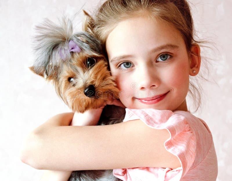 Bambino sorridente della bambina che tiene e che gioca con l'Yorkshire terrier del cucciolo fotografia stock