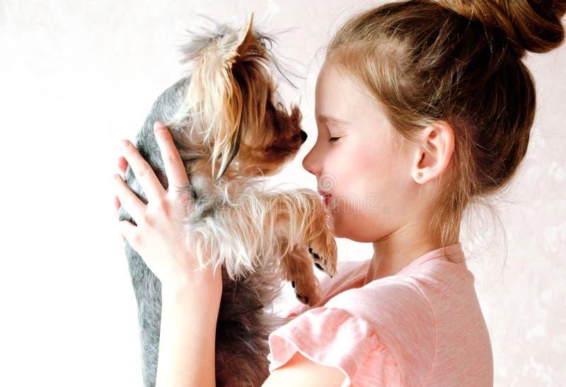 Bambino sorridente della bambina che tiene e che gioca con l'Yorkshire terrier del cucciolo fotografia stock libera da diritti