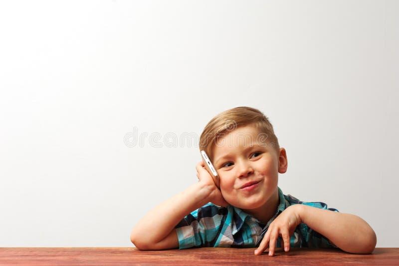 Bambino sorridente divertente che gioca con lo smartphone fotografia stock