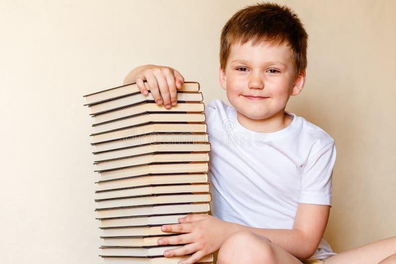 Bambino sorridente e molti libri fotografie stock libere da diritti