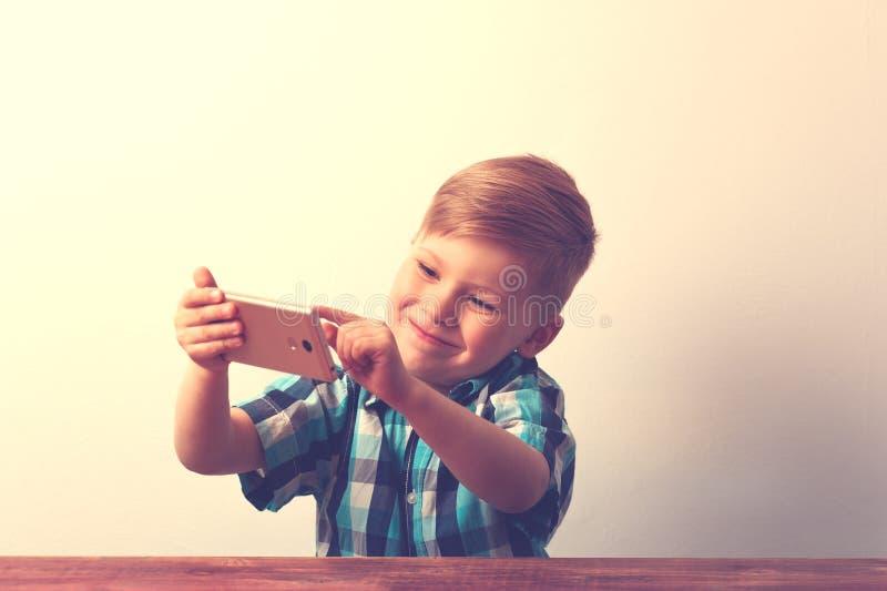 Bambino sorridente felice con lo smartphone in mani fotografia stock libera da diritti