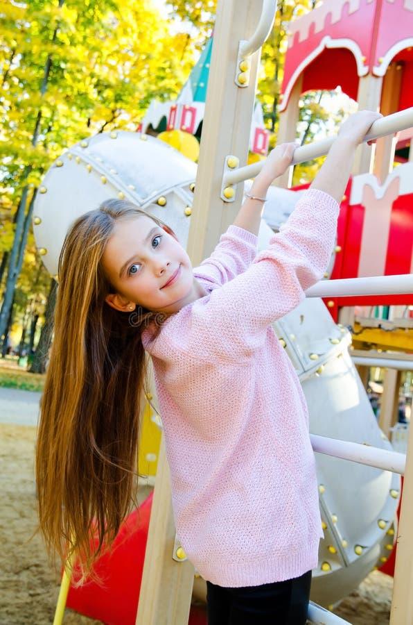 Bambino sorridente felice della bambina di cutu sull'attrezzatura del campo da giuoco fotografia stock libera da diritti