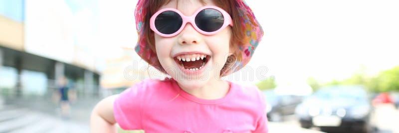 Bambino sorridente felice della ragazza in ritratto all'aperto degli occhiali da sole fotografie stock