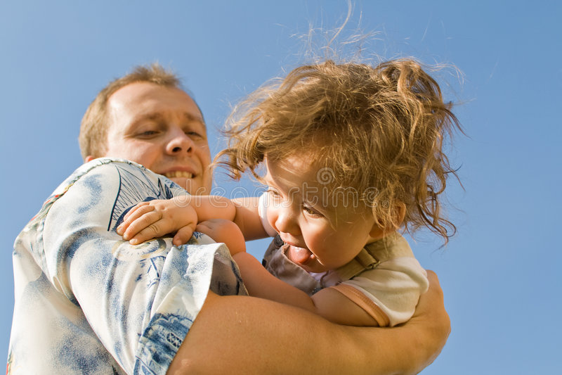 Bambino sorridente in mani del padre fotografia stock libera da diritti