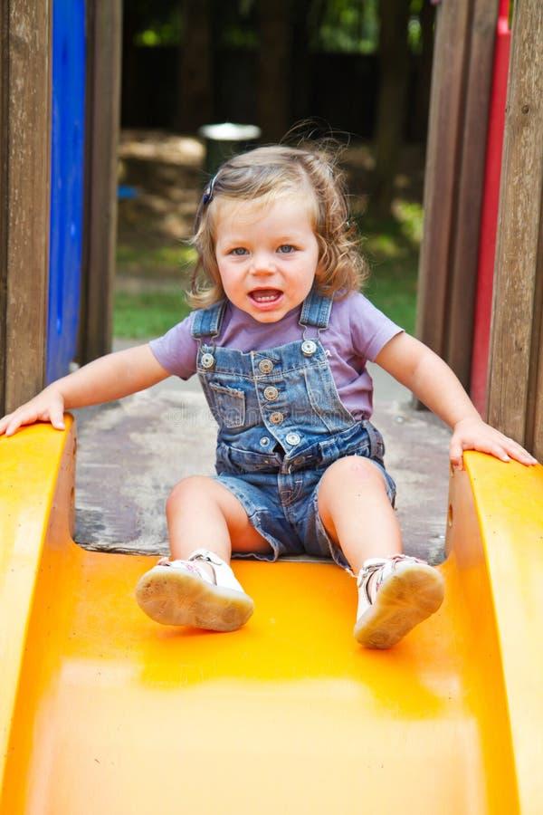 bambino sorridente su area del campo da giuoco dello scorrevole immagini stock libere da diritti
