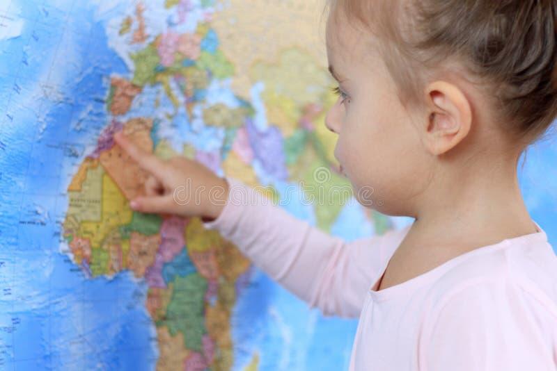Bambino sorridente sveglio che cerca posto sulla mappa di mondo fotografia stock libera da diritti