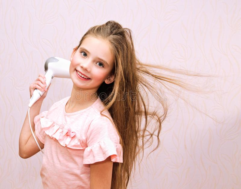 Bambino sorridente sveglio della bambina che asciuga i suoi capelli lunghi con il fon fotografia stock