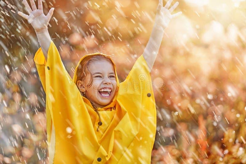 Bambino sotto la pioggia di autunno immagini stock libere da diritti