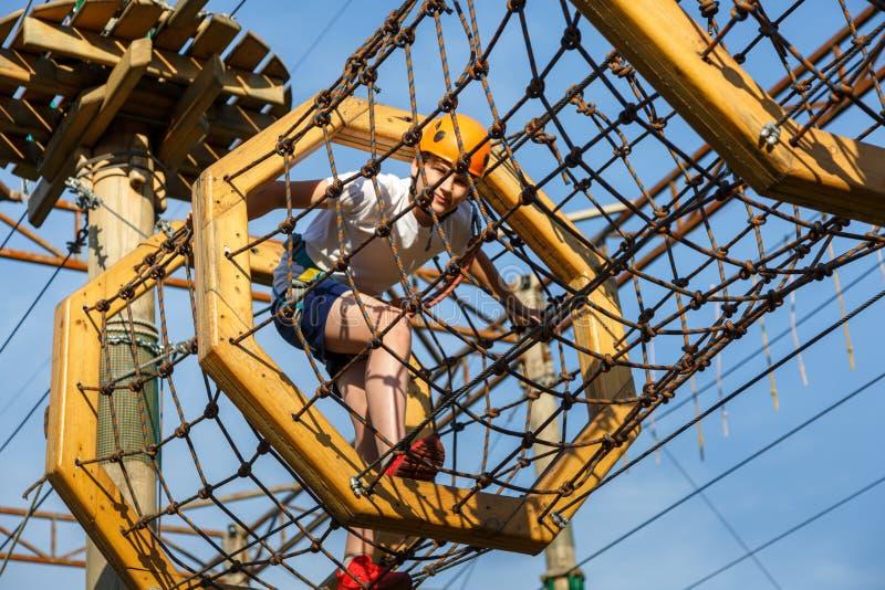 Bambino sportivo attivo in casco che fa attività nel parco di avventura con tutta l'attrezzatura rampicante I bambini attivi scal fotografia stock libera da diritti