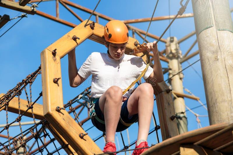 Bambino sportivo attivo in casco che fa attività nel parco di avventura con tutta l'attrezzatura rampicante I bambini attivi scal immagini stock