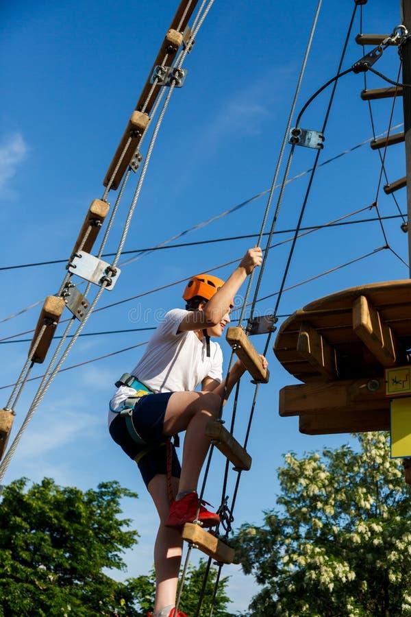Bambino sportivo attivo in casco che fa attività nel parco di avventura con tutta l'attrezzatura rampicante I bambini attivi scal immagine stock