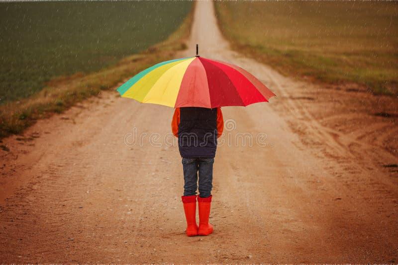 Bambino in stivali di gomma arancio che tengono ombrello variopinto sotto la pioggia in autunno Vista posteriore immagini stock libere da diritti