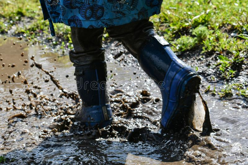 Bambino in stivali di gomma che giocano nel fango acqua del fango che spruzza e che corre campo da giuoco ambientale divertente i fotografia stock