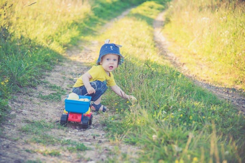 Bambino su una strada che gioca con l'automobile del giocattolo immagine stock