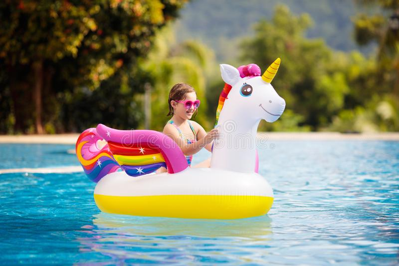 Bambino sul galleggiante dell'unicorno nella piscina Nuotata dei bambini fotografie stock libere da diritti
