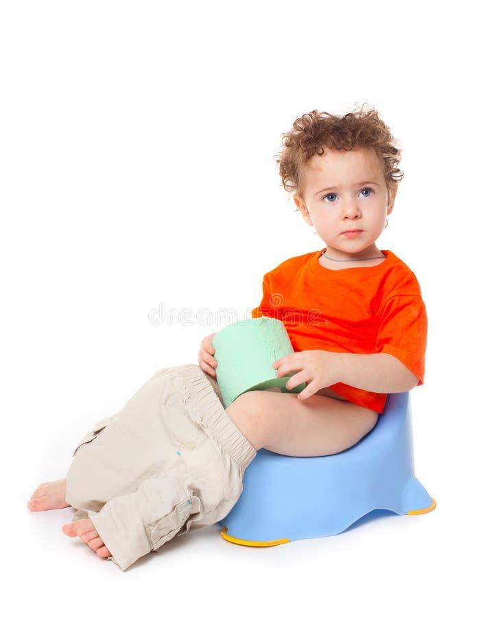 Bambino sul potty con la carta del lavabo fotografie stock libere da diritti