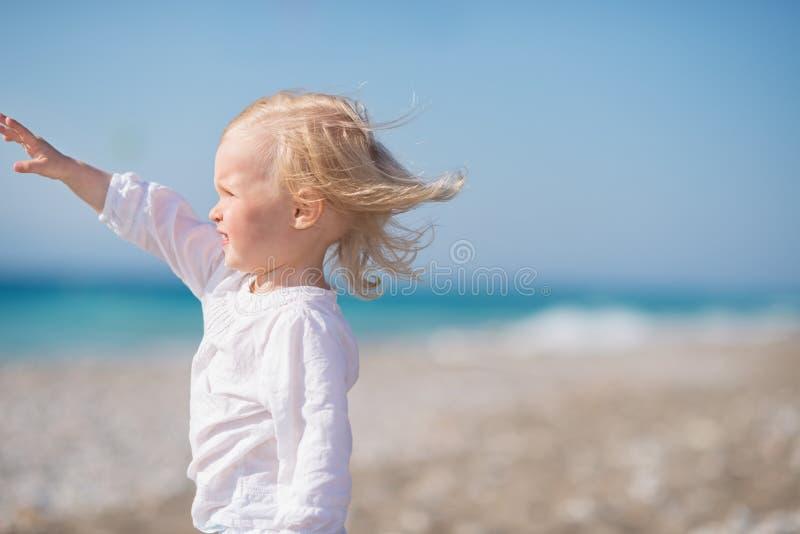 Bambino sulla spiaggia che esamina la distanza immagini stock