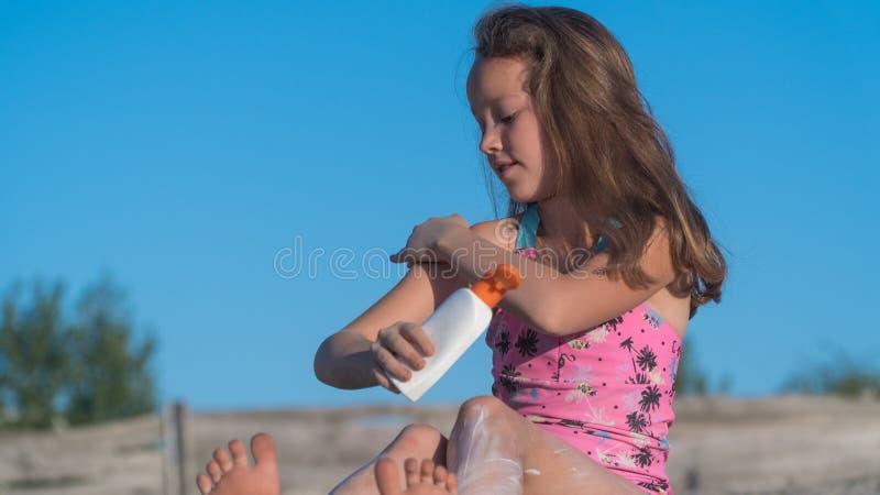 Bambino sulla spiaggia Crema dalla solarizzazione Protezione dal sole fotografia stock libera da diritti