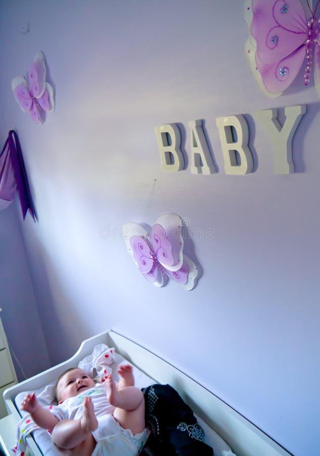 Bambino sulla tabella del cambiamento nella stanza viola dei bambini fotografie stock