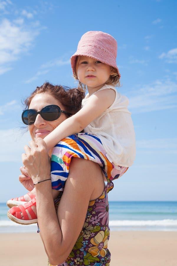 Bambino sulle spalle della madre fotografia stock