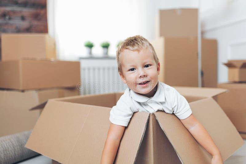 Bambino sveglio che aiuta le scatole fuori di imballaggio immagine stock libera da diritti