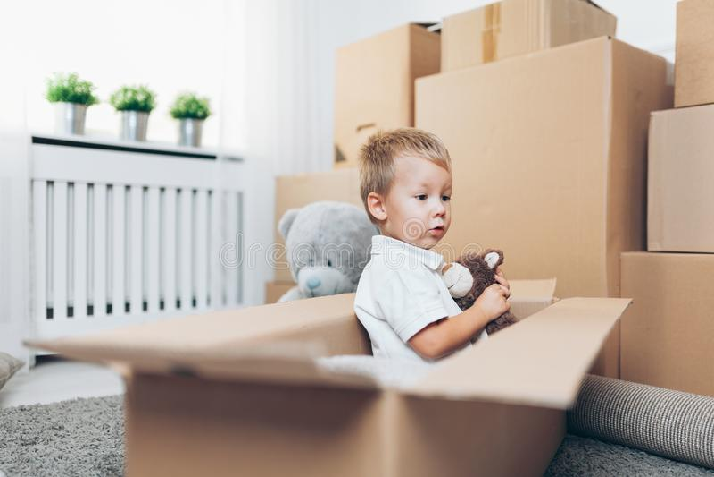 Bambino sveglio che aiuta le scatole fuori di imballaggio immagine stock